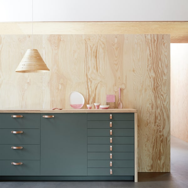 A kitchen unit with differently sized drawers and a cabinet made up of BODARP kitchen fronts in a matte grey-green.