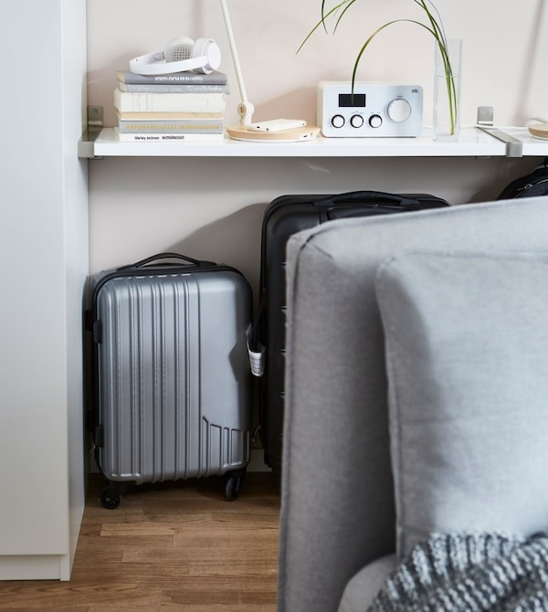 Suitcases stored behind a light grey IKEA VALLENTUNA modular sofa unit and underneath a white mounted shelf.