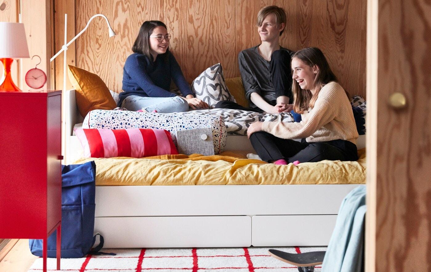 Drei Teenager sitzen auf einem SLÄKT Bettgestell mit Unterbett und Bluetooth-Lautsprecher in einem hellen Zimmer mit Holzwänden. Neben dem Bett steht ein kleiner, roter Schrank.