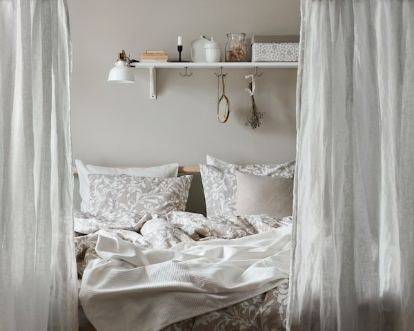 A bedroom with gray curtains, beige and white bedlinen, and matching pillows