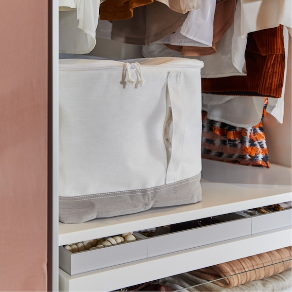A white wardrobe with drawers and a LACKISAR white and beige/grey storage case.
