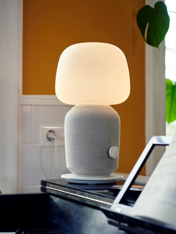 A SYMFONISK table lamp with WiFi speaker on a piano, with a white and orange wall in the background and a green plant.
