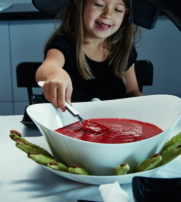 A little girl dressed as a witch scoops some red soup.