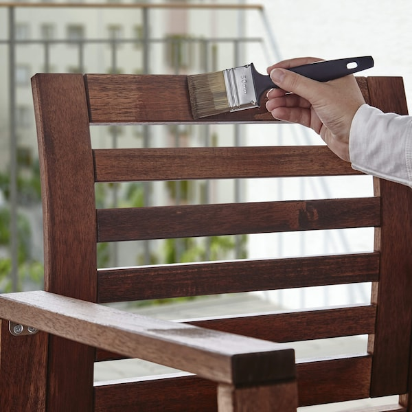 A hand holds a black paint brush that is applying brown wood stain to a wooden, outdoor chair.