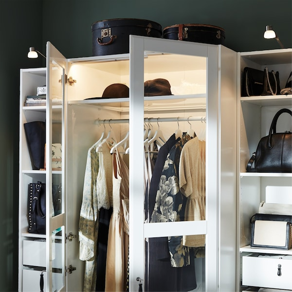 A white PAX wardrobe with glass doors, aluminium-coloured lighting strips and nickel-plated cabinet lighting.