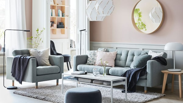 Light green sofa with matching armchair in a pink living room