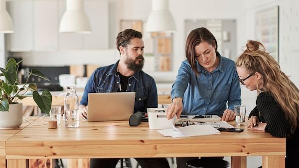 En företagsinredare står tillsammans med kund i ett tomt rum och tittar på en ritning och planerar rummet.