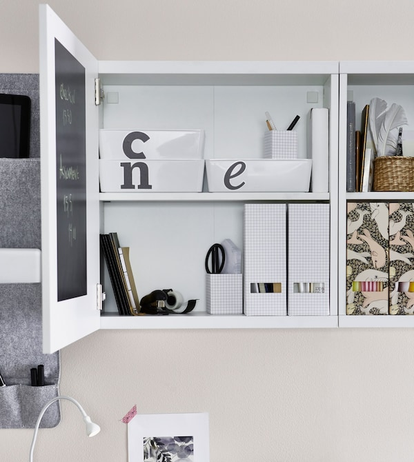 A white storage cabinet above a desk, opened to reveal labeled storage boxes within and white folder organisers inside.