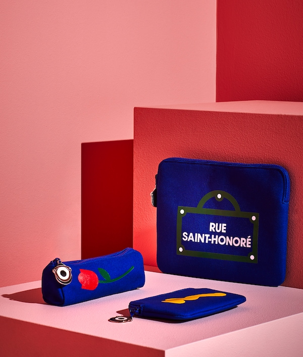 Three FÖRNYAD accessories in dark blue with different printed pattern. Media tablet case, pencil case and small case.