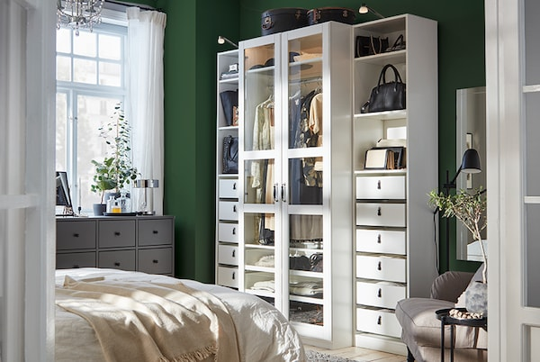 A bedroom with a white wardrobe with glass doors, a dark grey chest of drawers, and a grey-beige armchair.