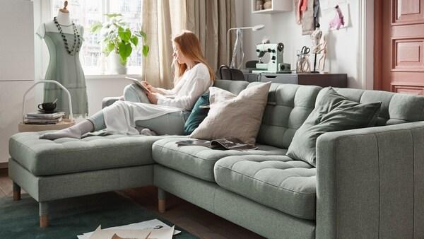 pokój dzienny, kobieta siedząca na jasnozielonej sofie LANDSKRONA