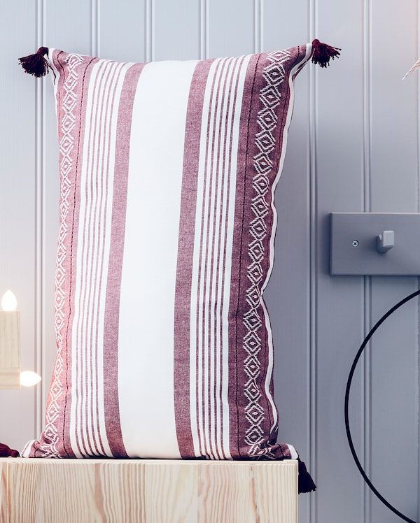 IKEA VINTERFEST pillow case with red and white coloured stripes and other patterns on a wooden bench.