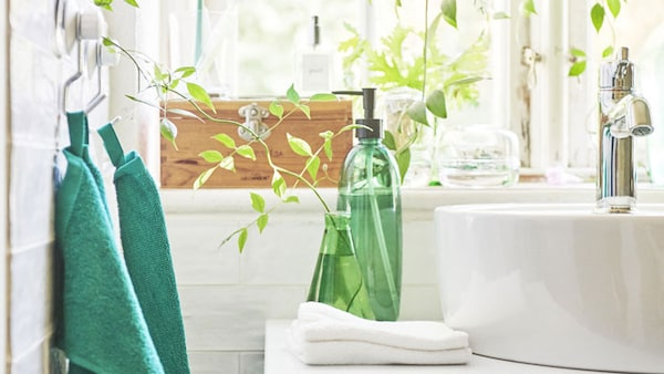 A white bathroom with green towels and green soap dispenser.