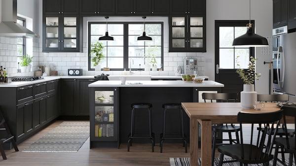 Ett LERHYTTAN svart kök med en köksö i mitten och två barstolar.