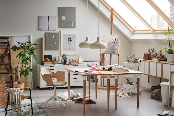 A sunlit office space, decorated in white with beige wood furniture.