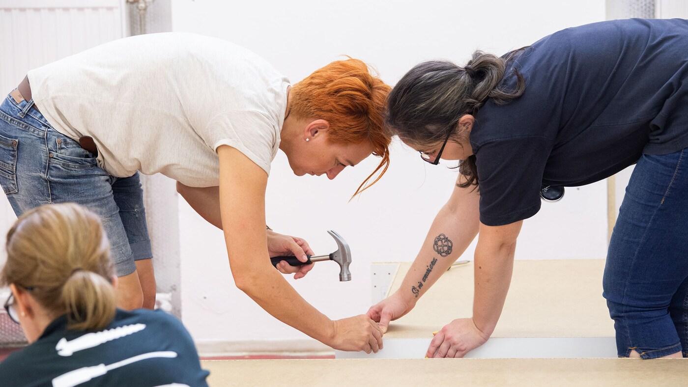 Két nő közösen szereli össze az IKEA bútorokat.