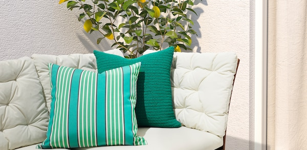 Green striped and green crochet outdoor cushions stacked on an outdoor lounge chair