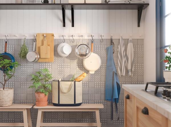 Nekoliko bijelih IKEA KUBBIS držača sa 7 kuka postavljenih na zid služe za vješanje kuhinjskog pribora.