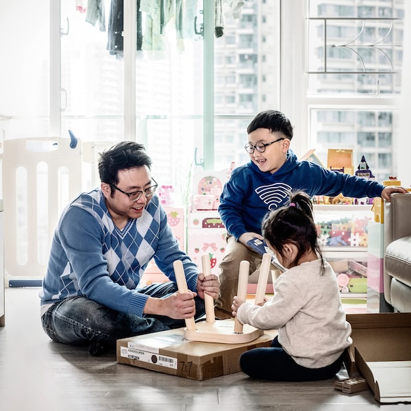 A father and two children are assembling an IKEA stool together in the living room.