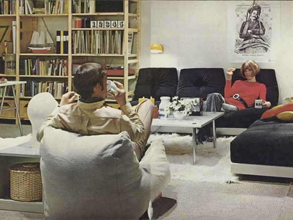 A 1980's living room with two seated people, with several IVAR shelving units in the background.