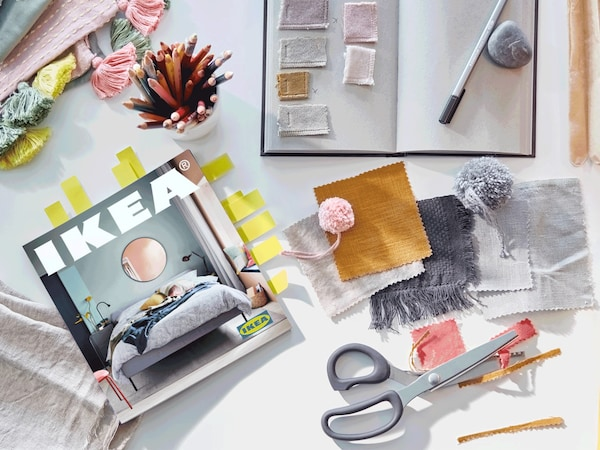A 2021 IKEA Catalogue, a note book for ideas, a pair of scissors, and pieces of fabric in pale pastels and mustard colours.