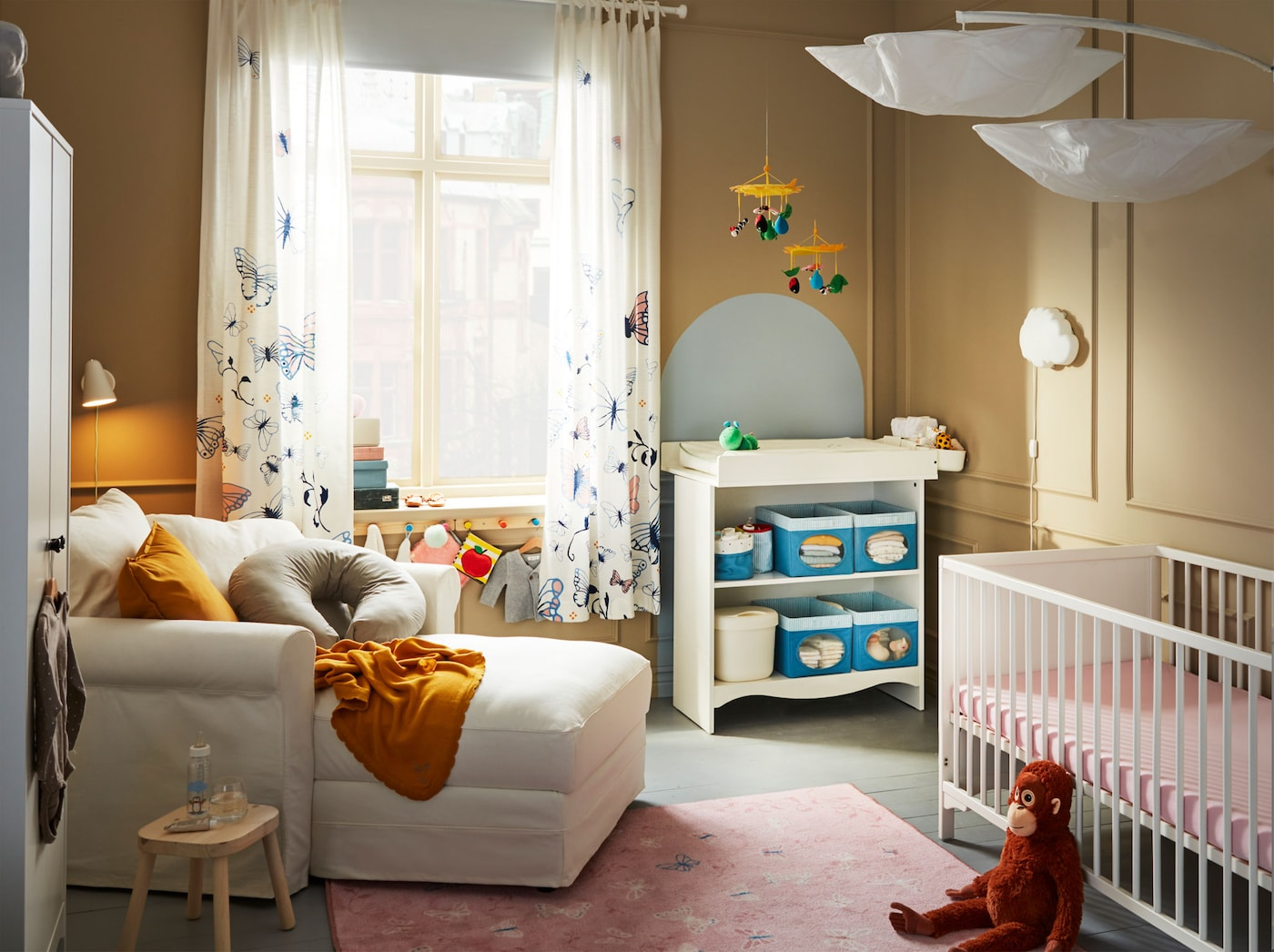 A baby bedroom with a white crib, a white chaise chair, a changing table, and a large window.