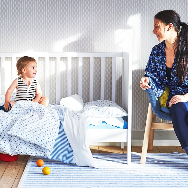 A baby sitting up in a SUNDVIK cot covered in blue and white bed linen looking at their mum who's at the end of the cot.