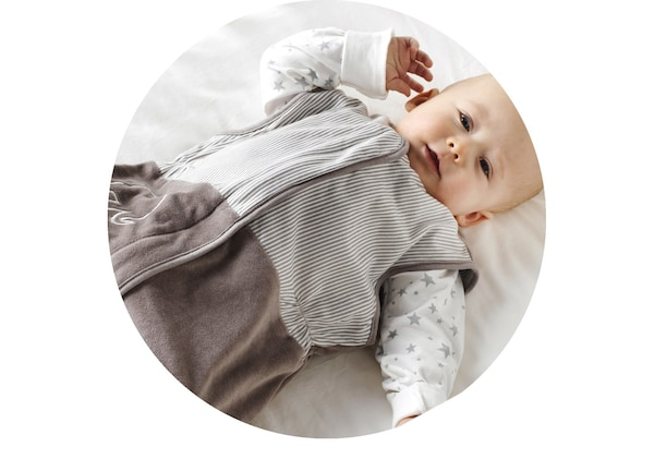 A baby that's lying down, wearing a beige and white IKEA sleeping bag made from responsibly grown cotton.