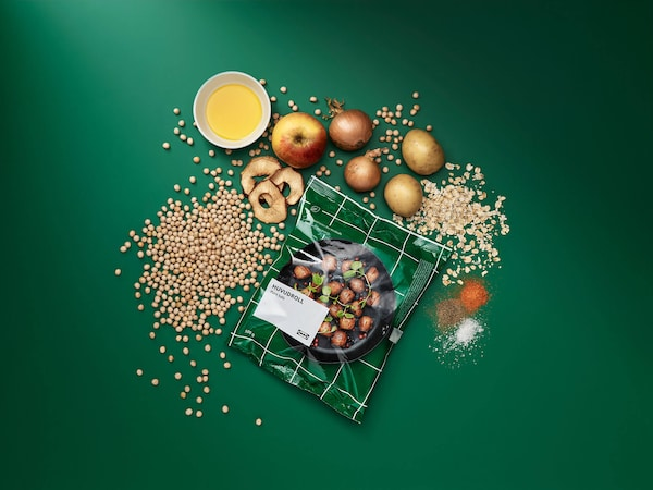 A bag of IKEA plant balls with various grains, vegetables, spices, and an apple against a green background.