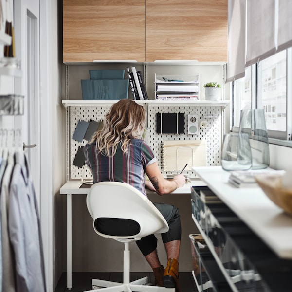 A balcony area with a wall of windows with a person working in a home working space, with cupboards and shelves on the wall.