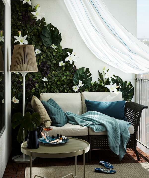 A balcony furnished with a two-seat sofa, artificial-flower wall and draped with a weatherproofing shower curtain.