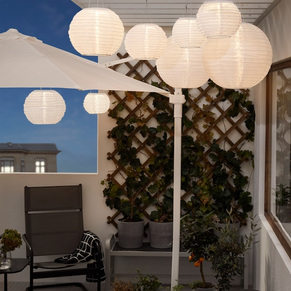 A balcony in the evening. Several SOLVINDEN pendant lamps hang from the ceiling, and they create a cosy mood lighting.