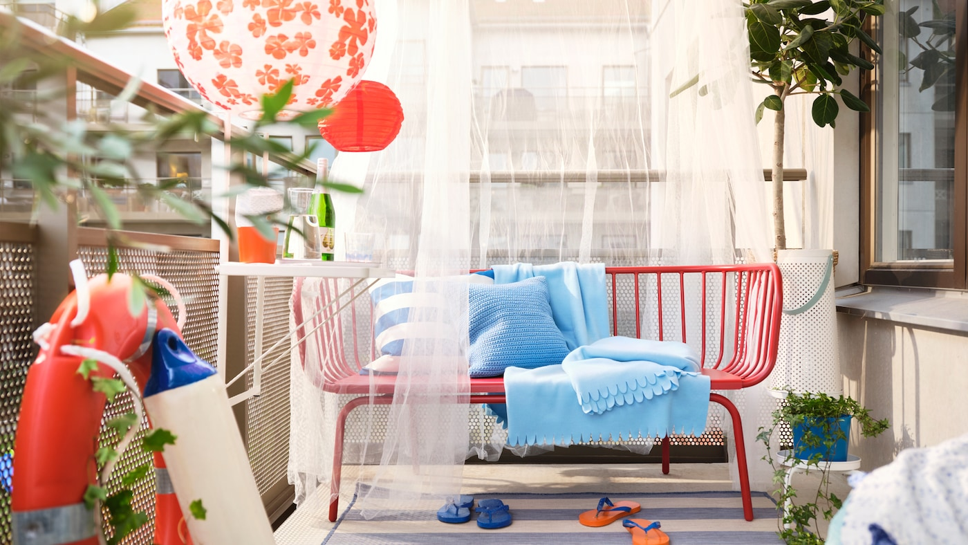 A balcony with a red BRUSEN outdoor sofa with blue cushions and throws, a TORPARÖ balcony table and solar powered LED lamps.