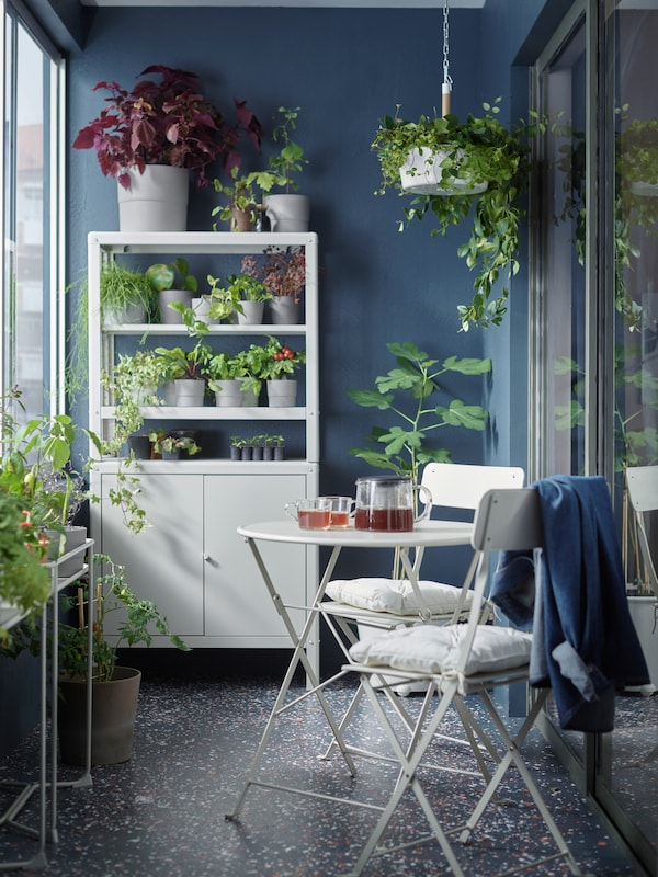 A balcony with a white table and two chairs, some white storage holding plants and plant pots, and a hanging plant.