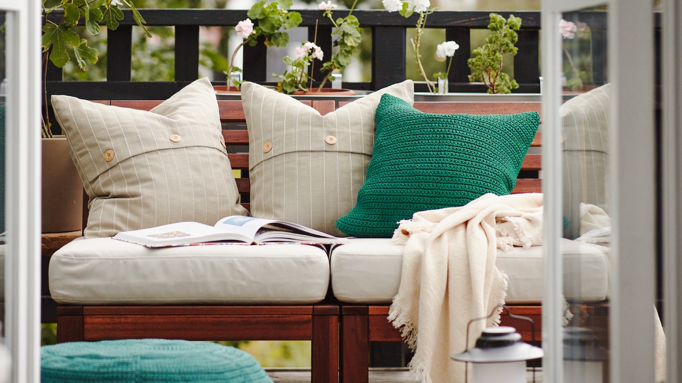 A balcony with a wooden outdoor sofa with white and green cushions, a throw and an open book on it, green plants behind.