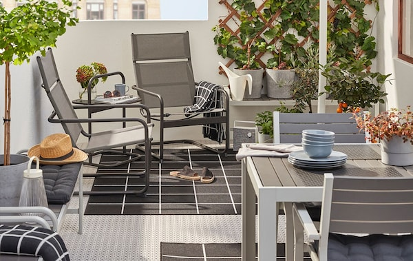 A balcony with outdoor furniture for lounging and dining.