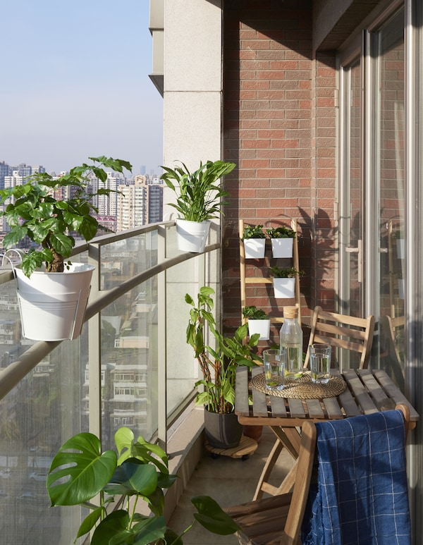 A balcony with plants and a table and chairs.