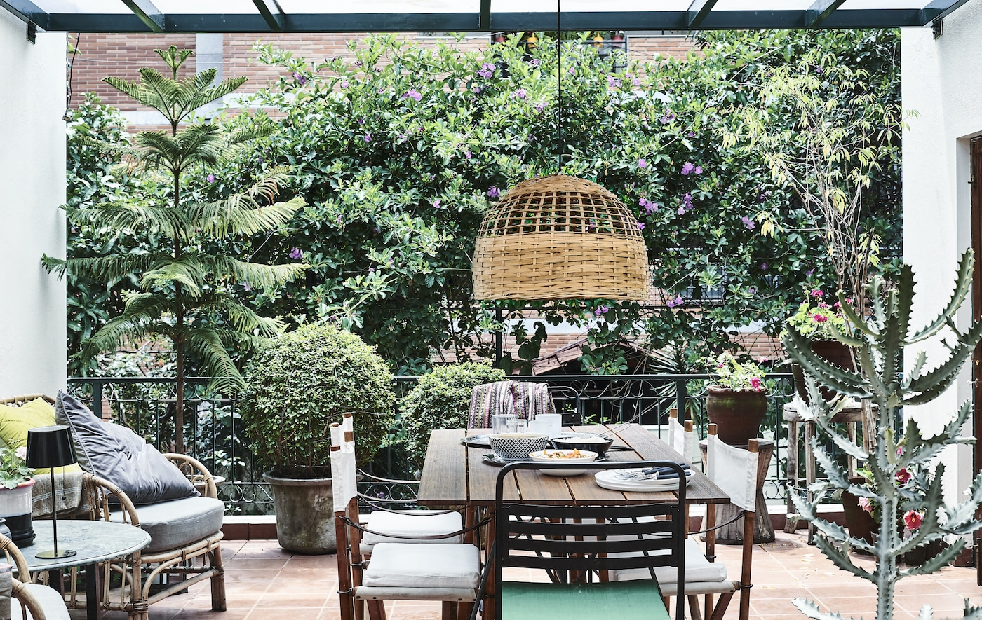 A balcony with plants, chairs, table and pendant lamp.