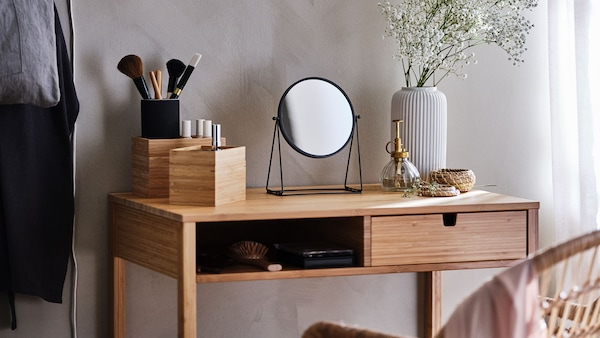 A bamboo dressing table with a small stand mirror, makeup brushes, and a vase of dried flowers.