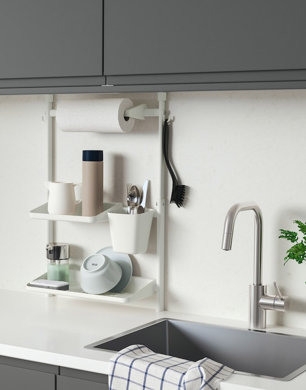 A basic kitchen solution with white drawers, red metal shelves for standing and wall-hung storage, and a low fridge.
