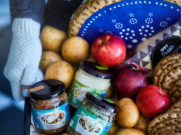 A basket of food including cheese, crisps, herring, apples and potatoes to donate