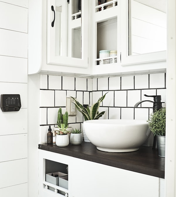 A bathroom area with white tiles and plants.