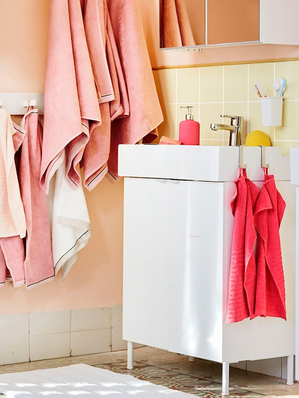 A bathroom chest with some towels in light salmon color