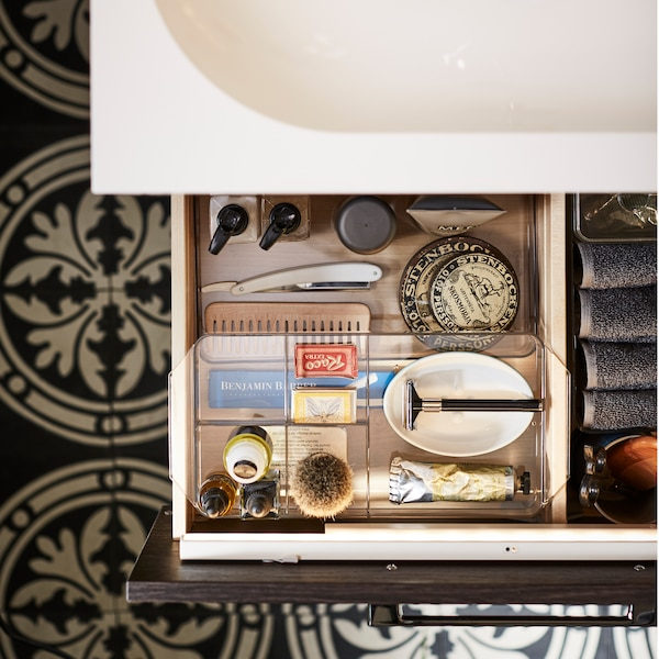 A bathroom drawer is open to show organised bathroom storage inside smoked organising boxes.