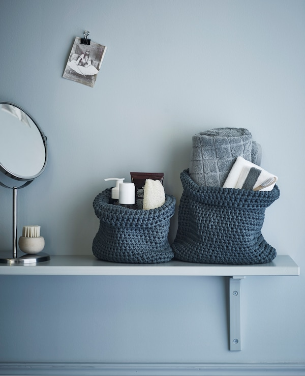 A bathroom shelf with toiletries and towels stacked in textile baskets