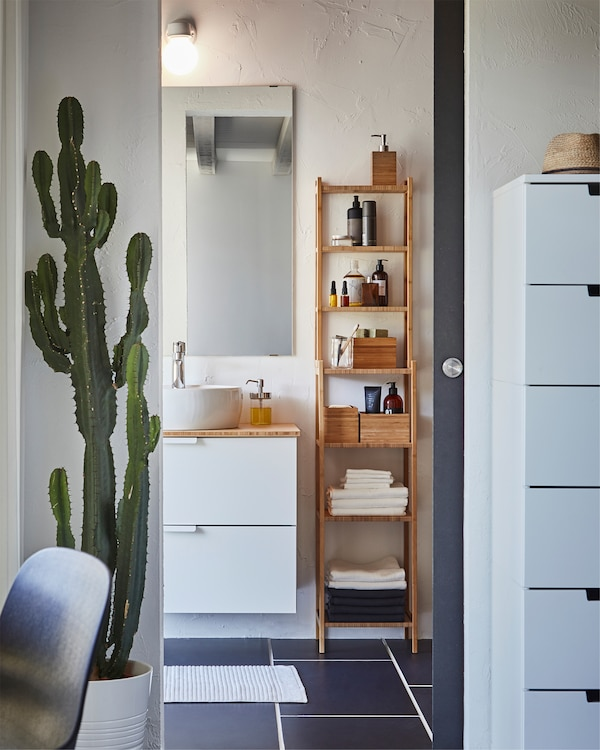 A bathroom where RÅGRUND shelving unit in bamboo is standing next to a white wash stand with a mirror on the wall above.