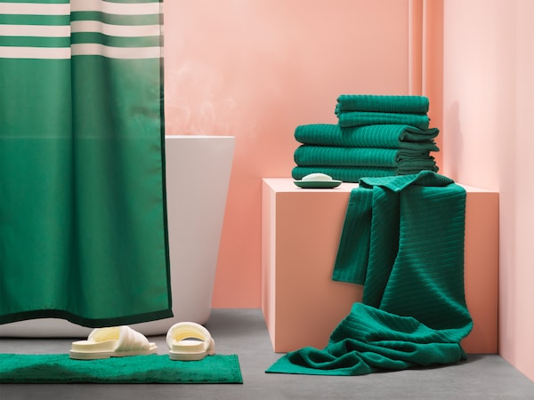 A bathroom with a green shower curtain, and some green bath towels stacked in a pile and hanging from a storage cabinet.