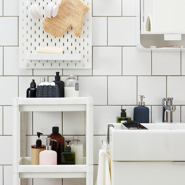A bathroom with a shelf unit and a wash-stand.