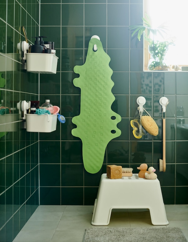 A bathroom with a step stool and a green PATRULL bathtub mat in the shape of a crocodile hanging from a suction cup hook.