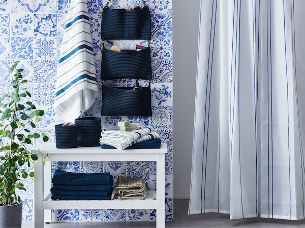A bathroom with a white HEMNES bench, several towels, blue baskets, a hanging storage solution and a shower curtain.